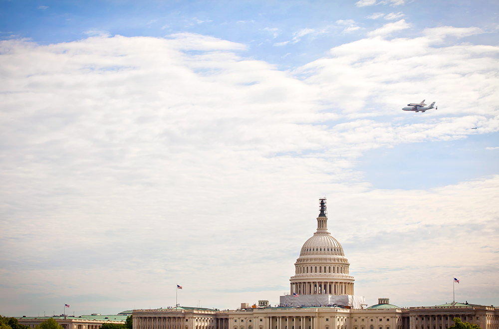 The space shuttle Discovery flies over the U.S. Capitol.